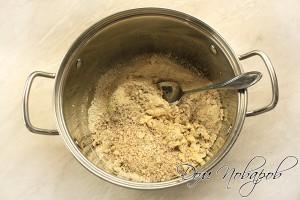 В глубокой емкости смешать хлопья, масло, желток с сахаром и панировочные сухари