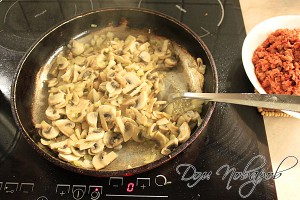 Обжарьте на растительном масле лук и грибы