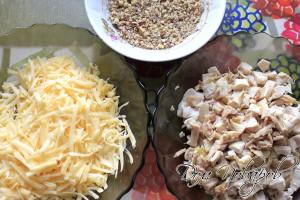 Натереть сыр, курицу нарезать кубиками, ядра орехов измельчить