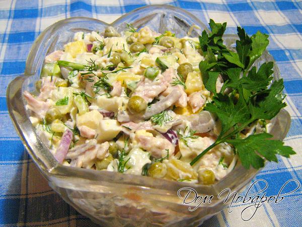 Переложите Оливье в салатник, украсьте зеленью