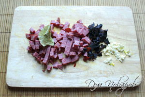 Кубиками измельчите колбасу, чернослив и чеснок