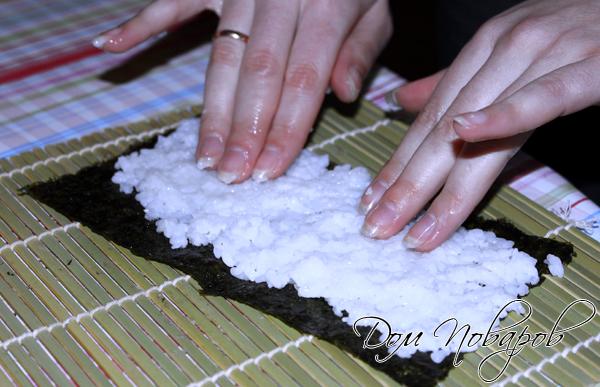 Распределите мокрыми руками рис по листу нори