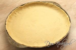 Раскатать тесто для пиццы в тонкий пласт.