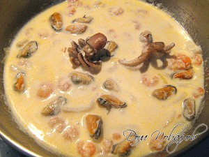 В сковородку с морепродуктами влейте сливки
