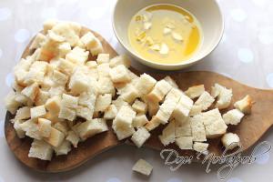 Свежий батон нарежьте кубиками, подготовьте чесночное масло