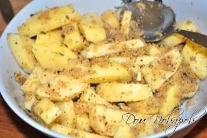 Перемешайте дольки картофеля и смесь